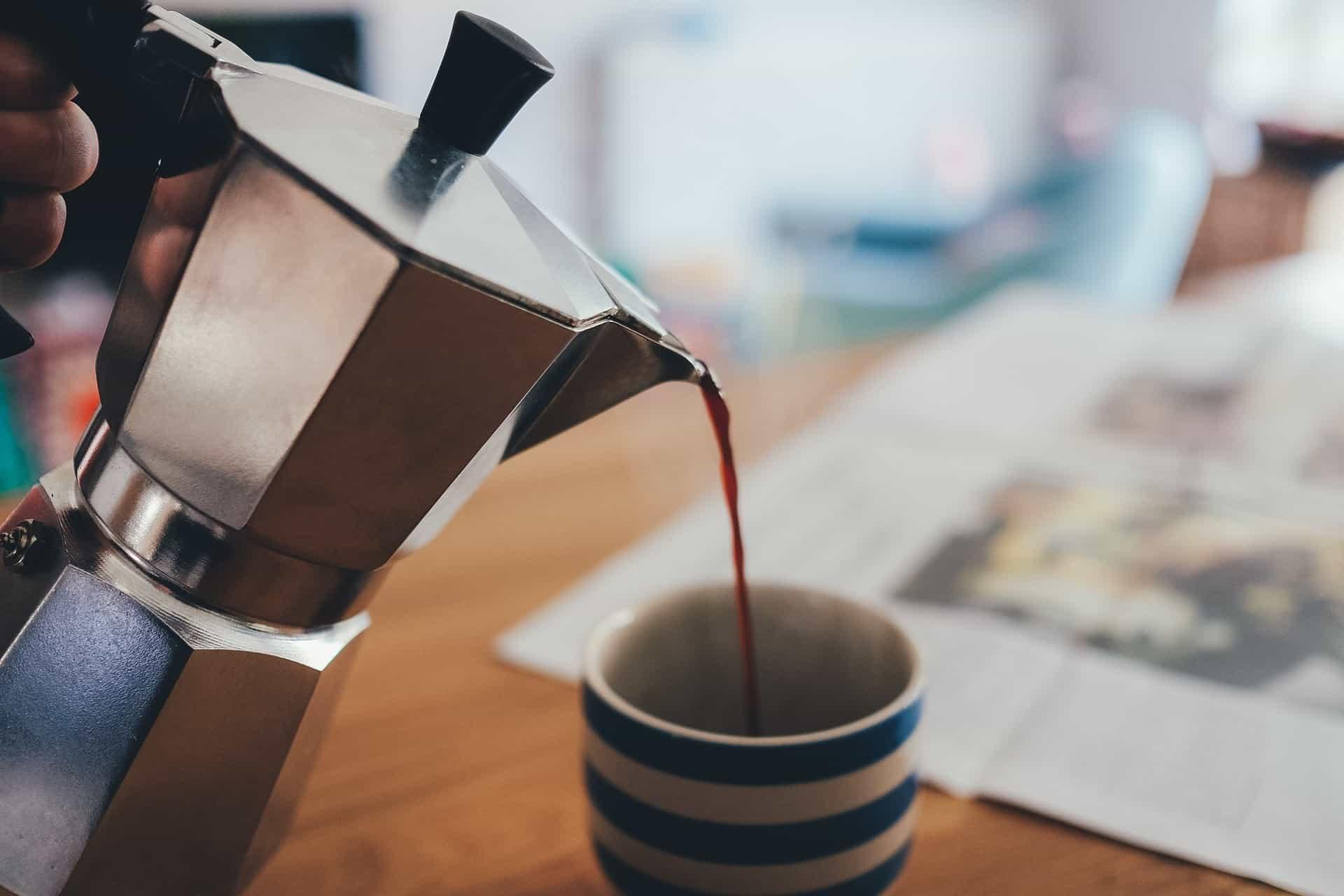 Café sendo servido na xícara com uma cafeteira italiana.