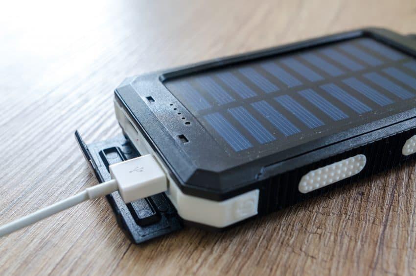 Imagem mostra carregador portátil solar em cima de uma superfície de madeira.