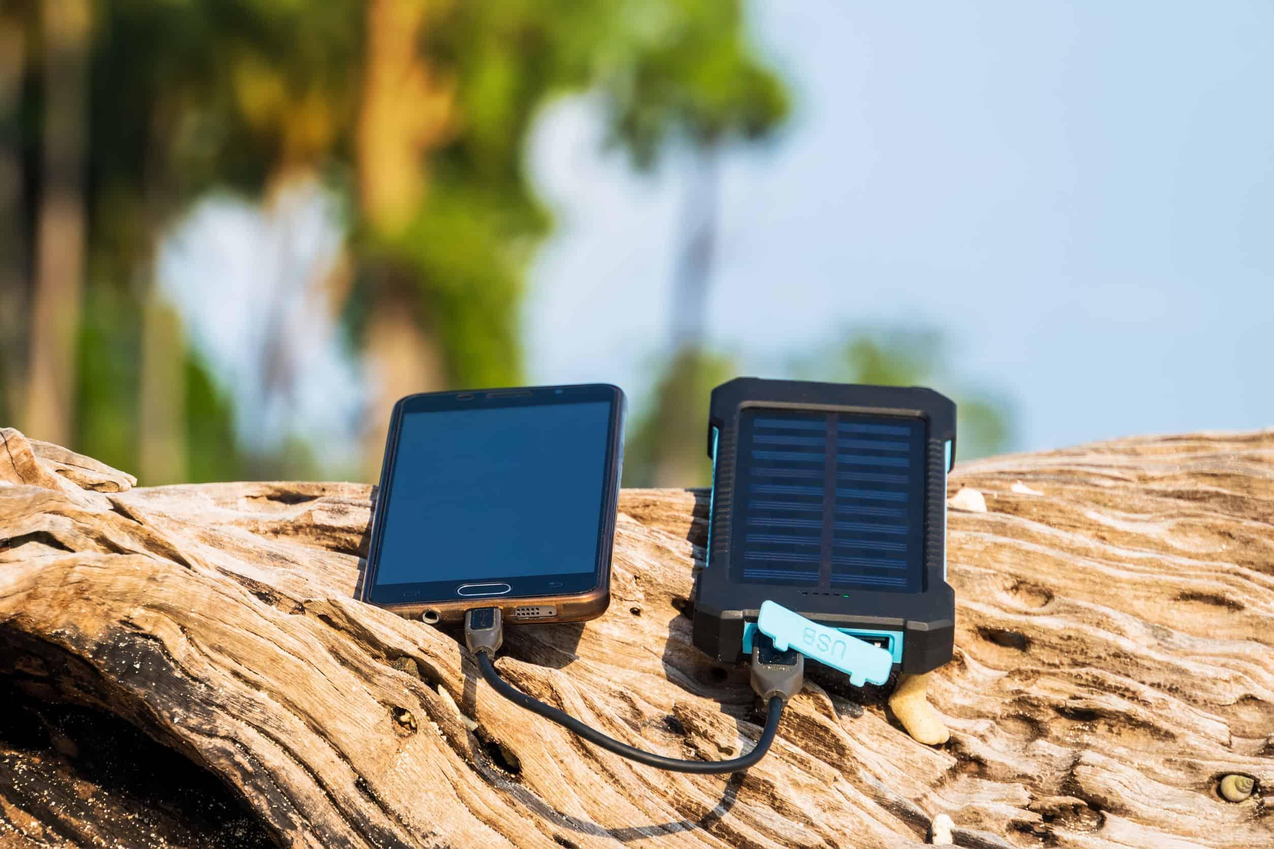 Carregador solar conectado a celular, em cima de um tronco de árvore.