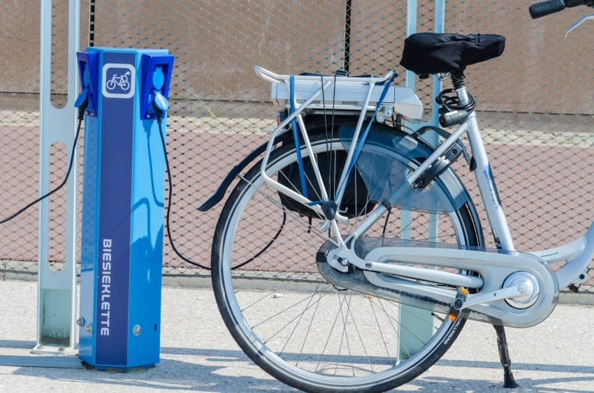 Imagem mostra bicicleta elétrica sendo carregada.