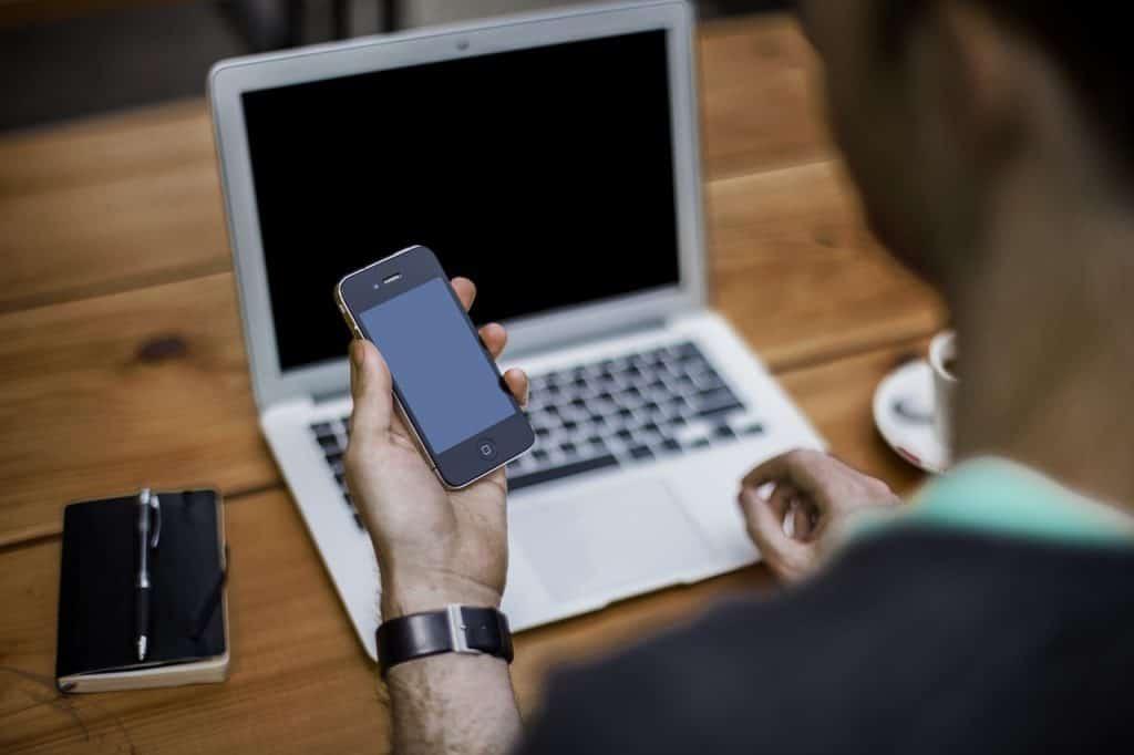 pessoa segurando o celular desligado em frente a um notebook