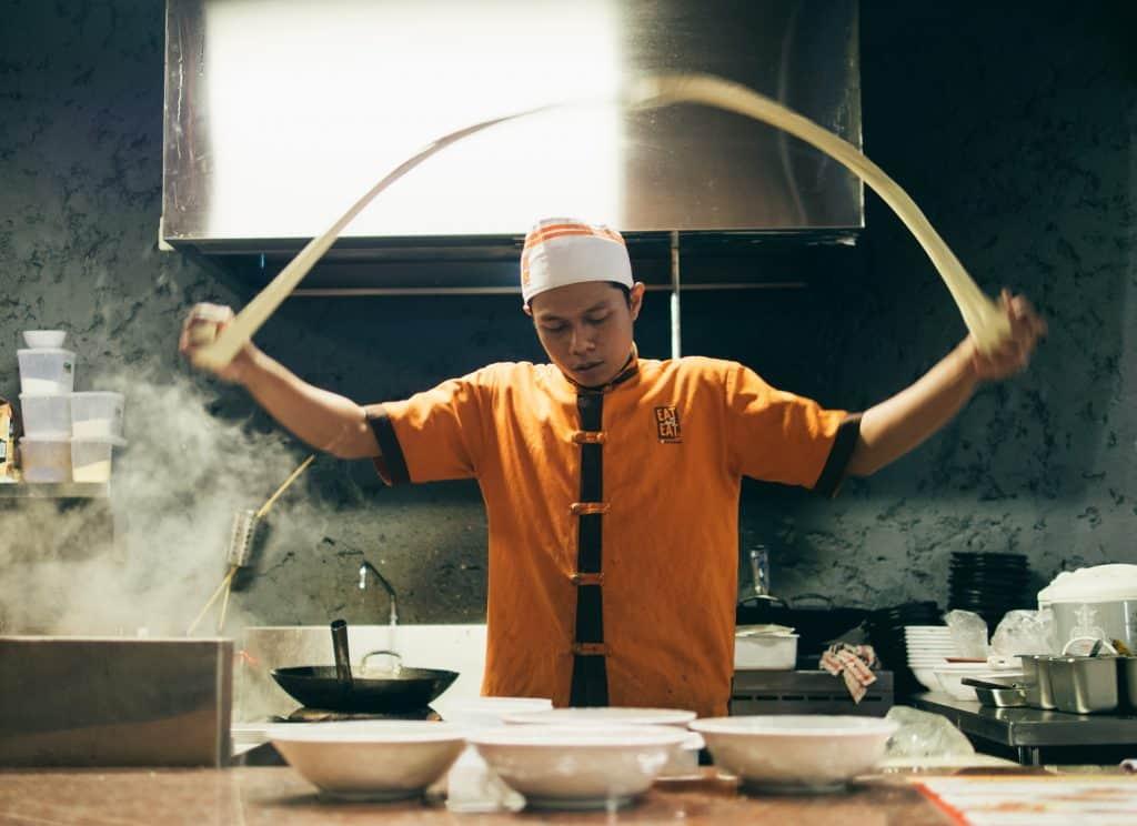 chef oriental cozinhando, jogando uma massa para cima