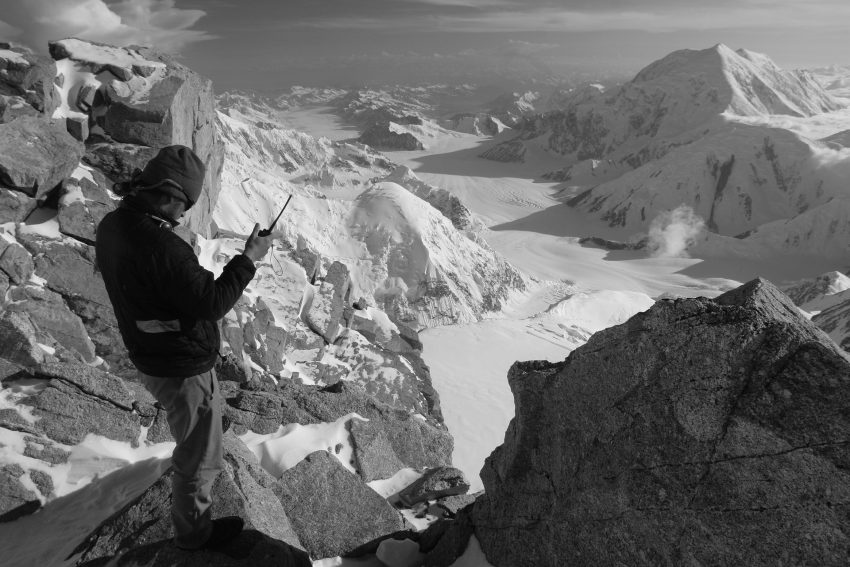 Image of a man on an ice mountain holding a radio communicator.