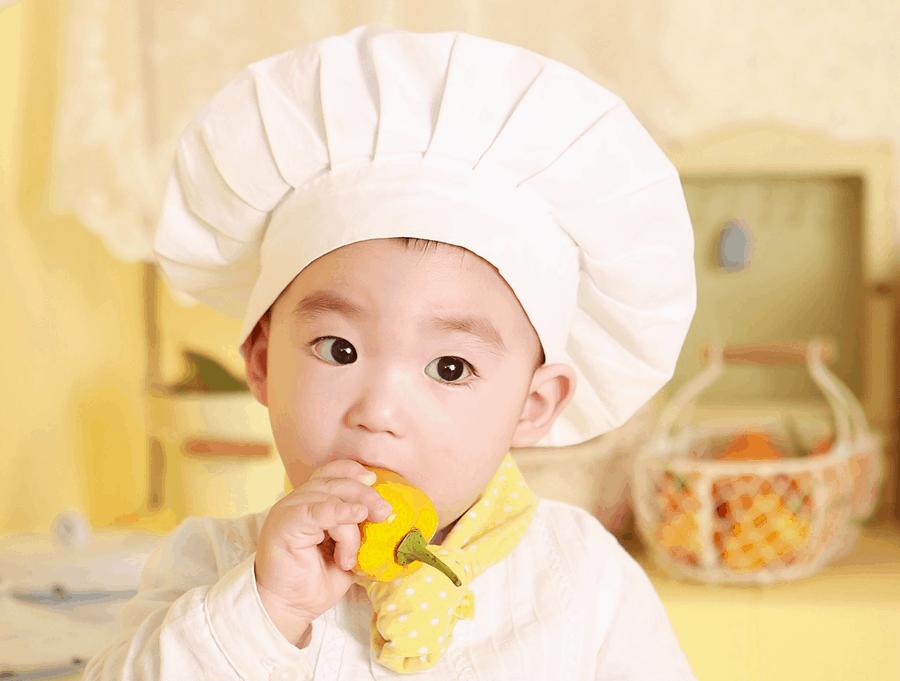 criança vestida de cozinheiro com pimentão na boca e cara de assustada