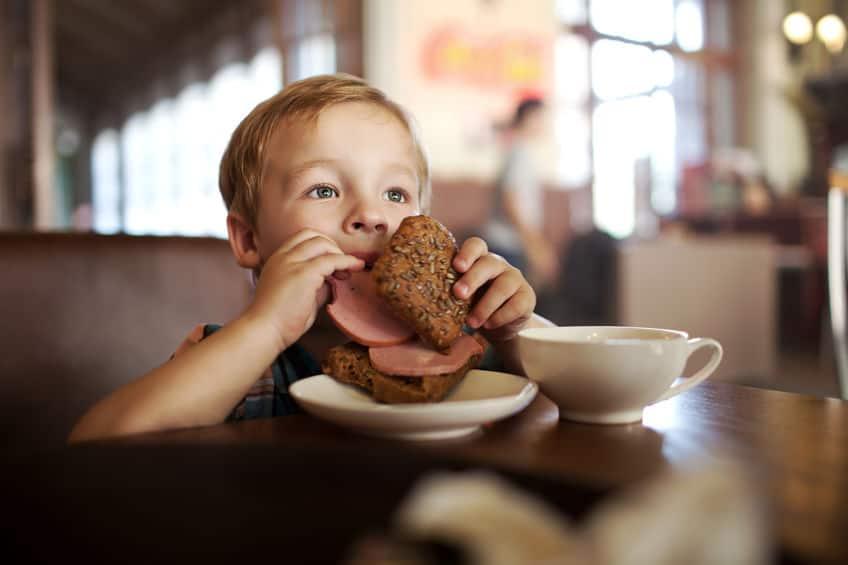 criança comendo pão sentada