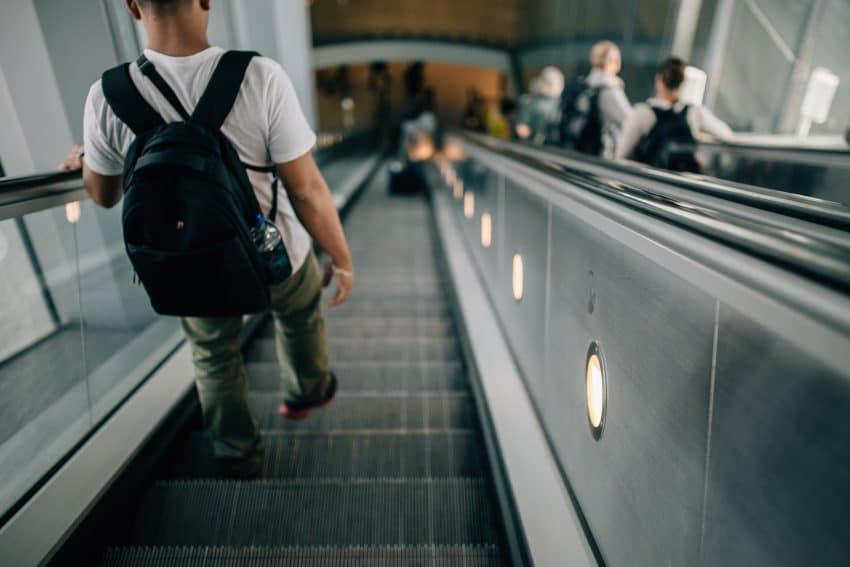 Imagem mostra uma pessoa descendo a escada rolante com uma mochila nas costas.