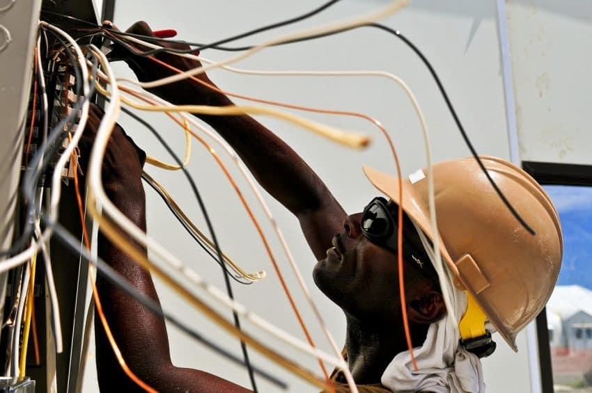 Eletricista trabalhando com diversos cabos elétricos em um quadro de força.