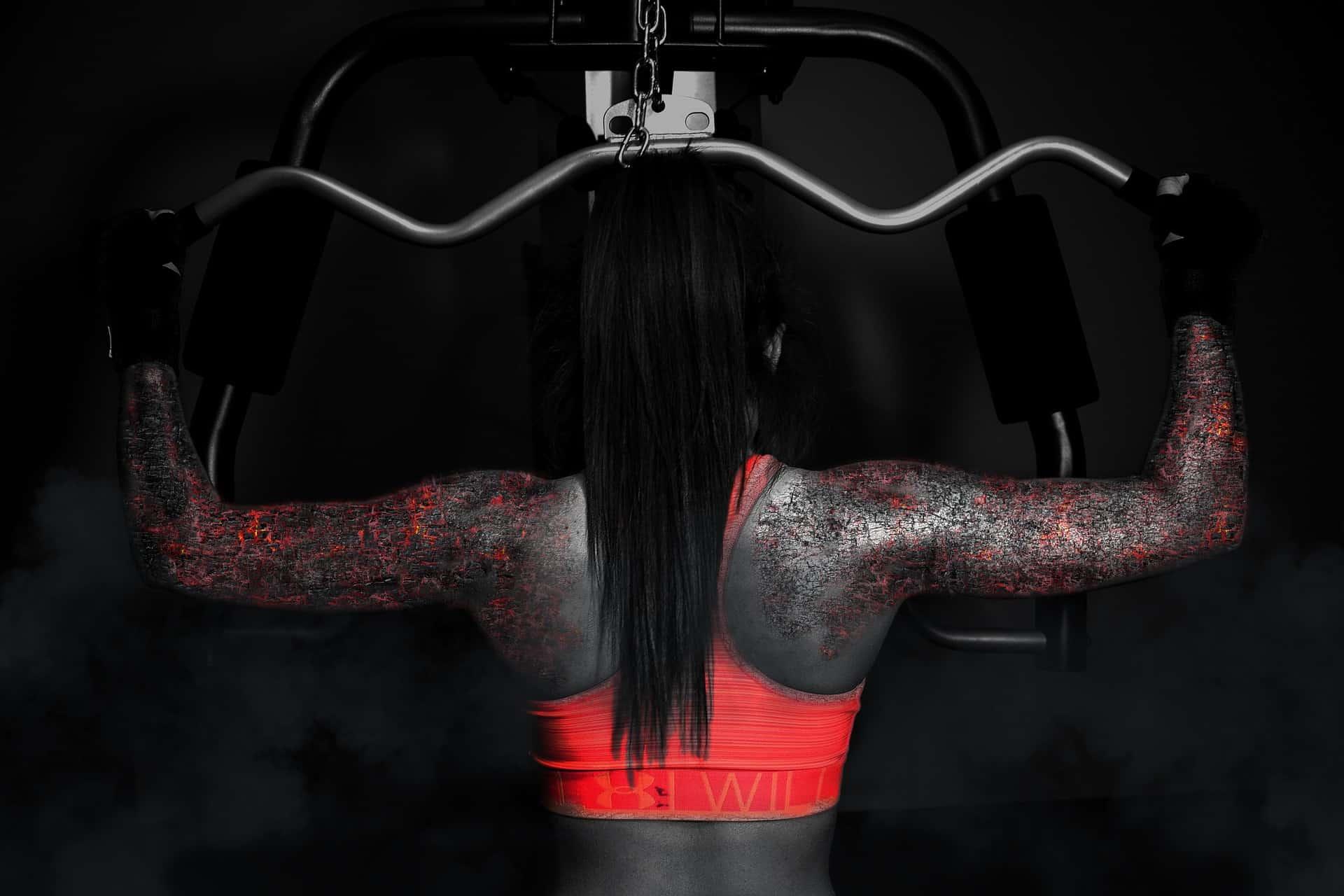 Mulher de costas com as costas tatuada treinando em uma estação de musculação.