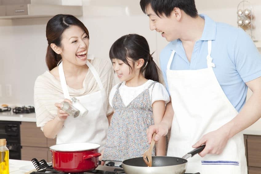 pai, mãe e filha cozinhando juntos