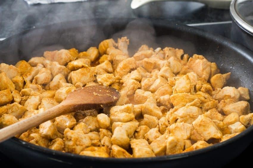 Frango frito na frigideira com colher de madeira.