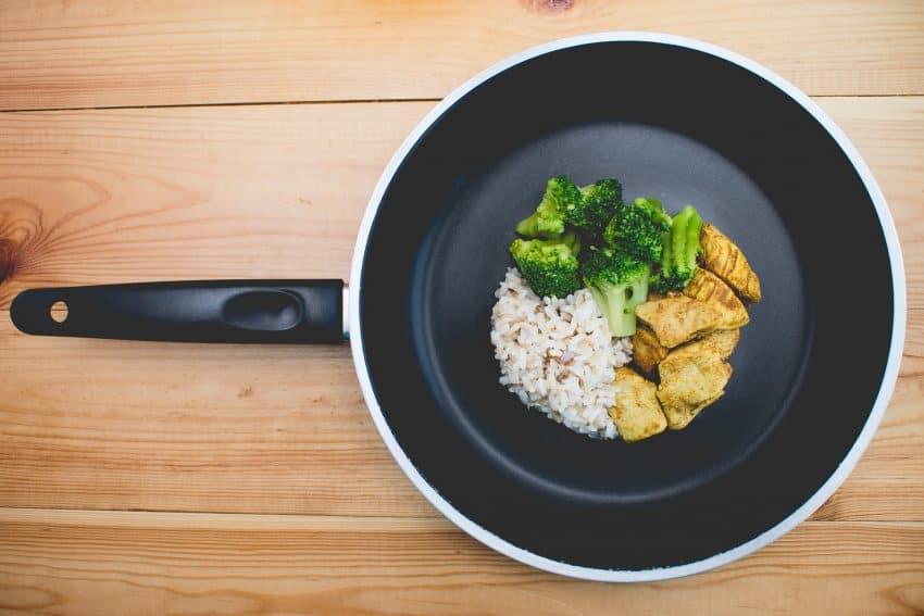 Imagem mostra frigideira vista de cima com arroz, brócolis e frango.