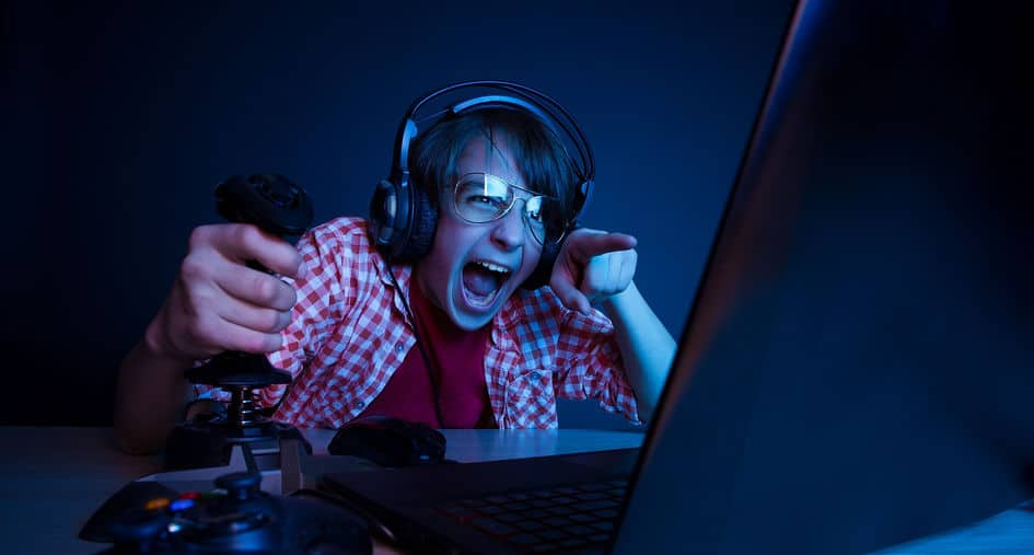 gamer em sala escura gritando em frente a um PC usando headset