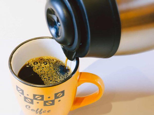 Imagem em close de café de uma garrafa térmica sendo despejado em uma caneca.