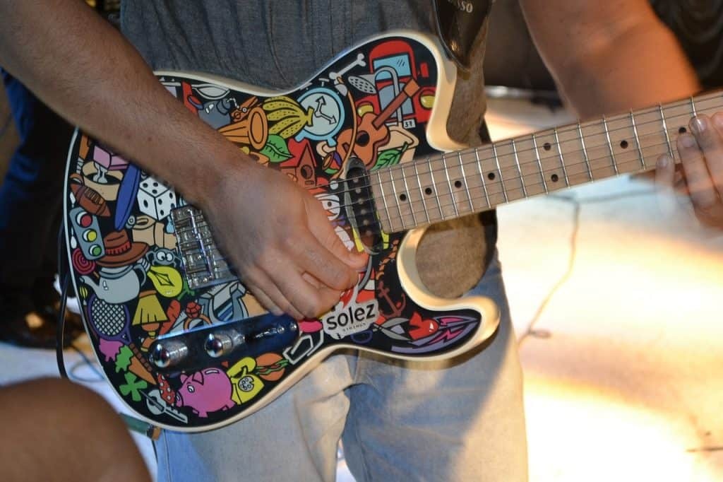 braços de uma homem tocando uma guitarra estampada
