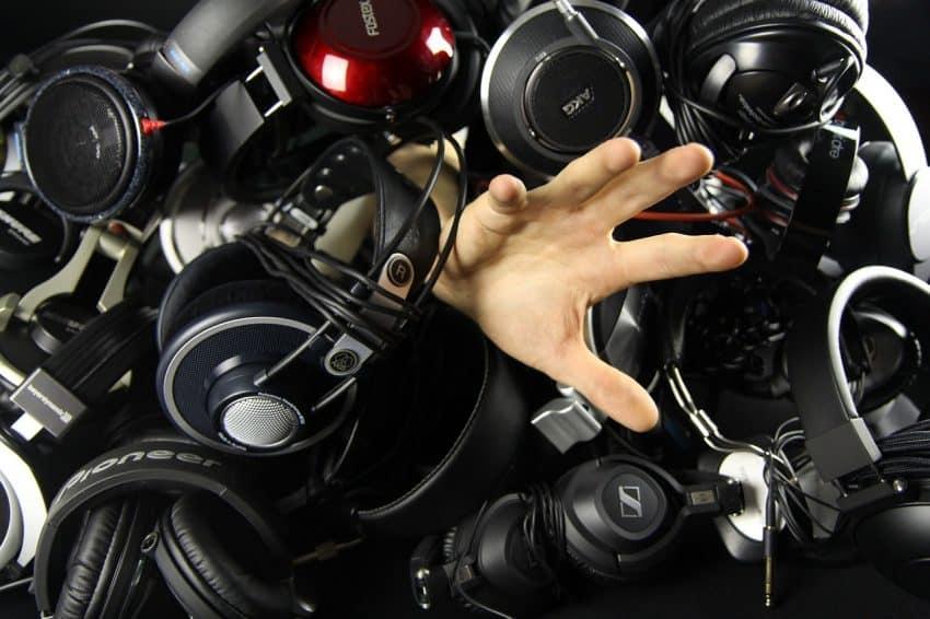 Imagem mostra mão saindo de uma barreira de headsets pretos.