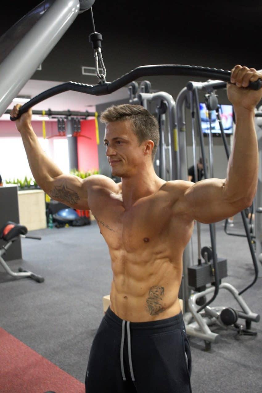 Homem segurando barra de exercícios em uma academia compacta.