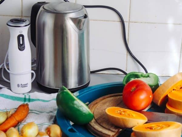 Imagem de jarra elétrica em cozinha, com legumes e outros utensílios.