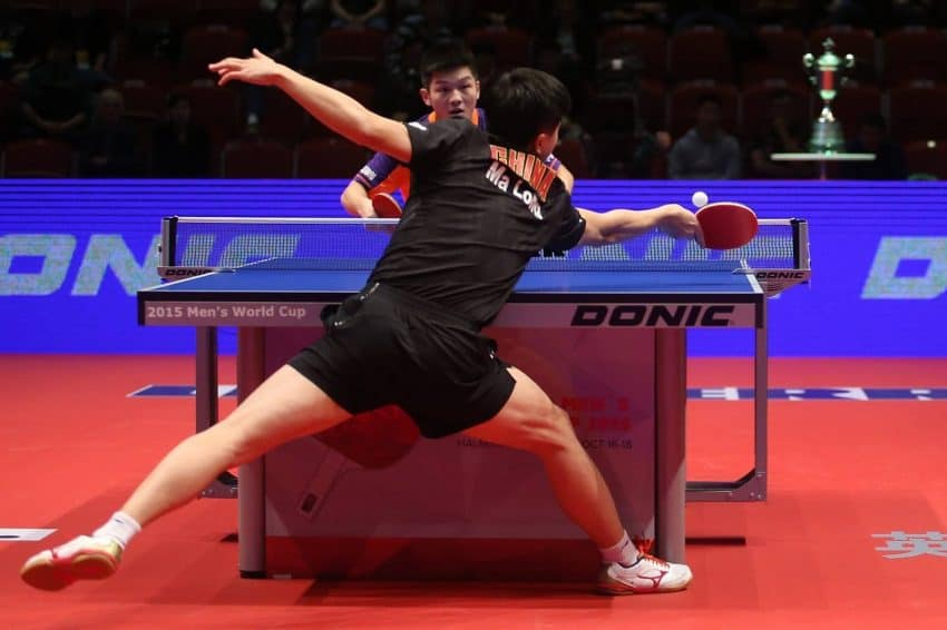 Imagem mostra dois profissionais jogando tênis de mesa em um campeonato.