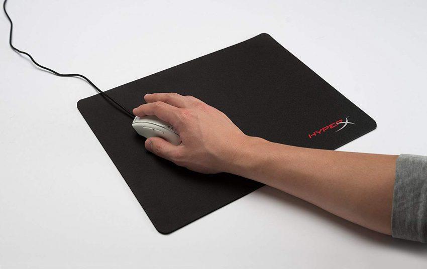Imagem mostra homem com a mão em um mouse e um mouse pad embaixo.