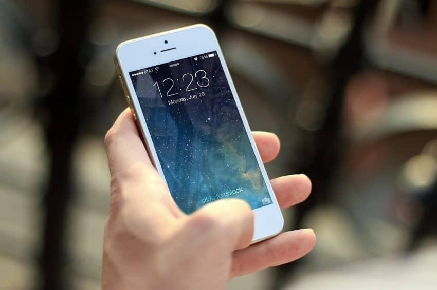Imagem mostra mão segurando iPhone.