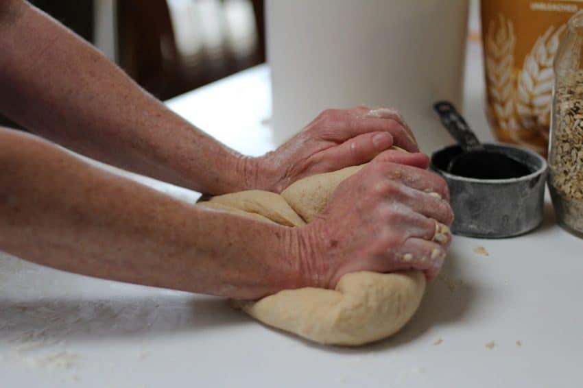 Mãos sovando massa de pão sobre bancada coberta de farinha.