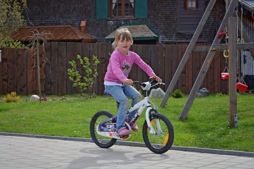 Imagem mostra menina pedalando com gramado ao fundo.