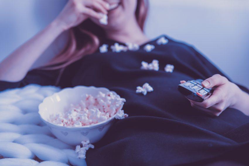 Imagem mostra menina assistindo TV enquanto come pipoca.
