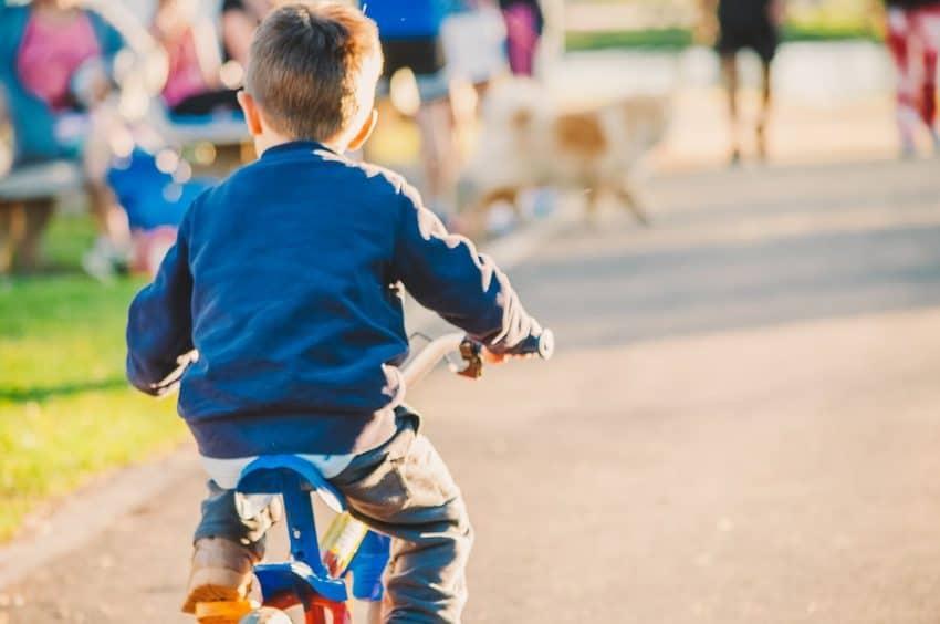 Menino pedalando em um parque em dia ensolarado.
