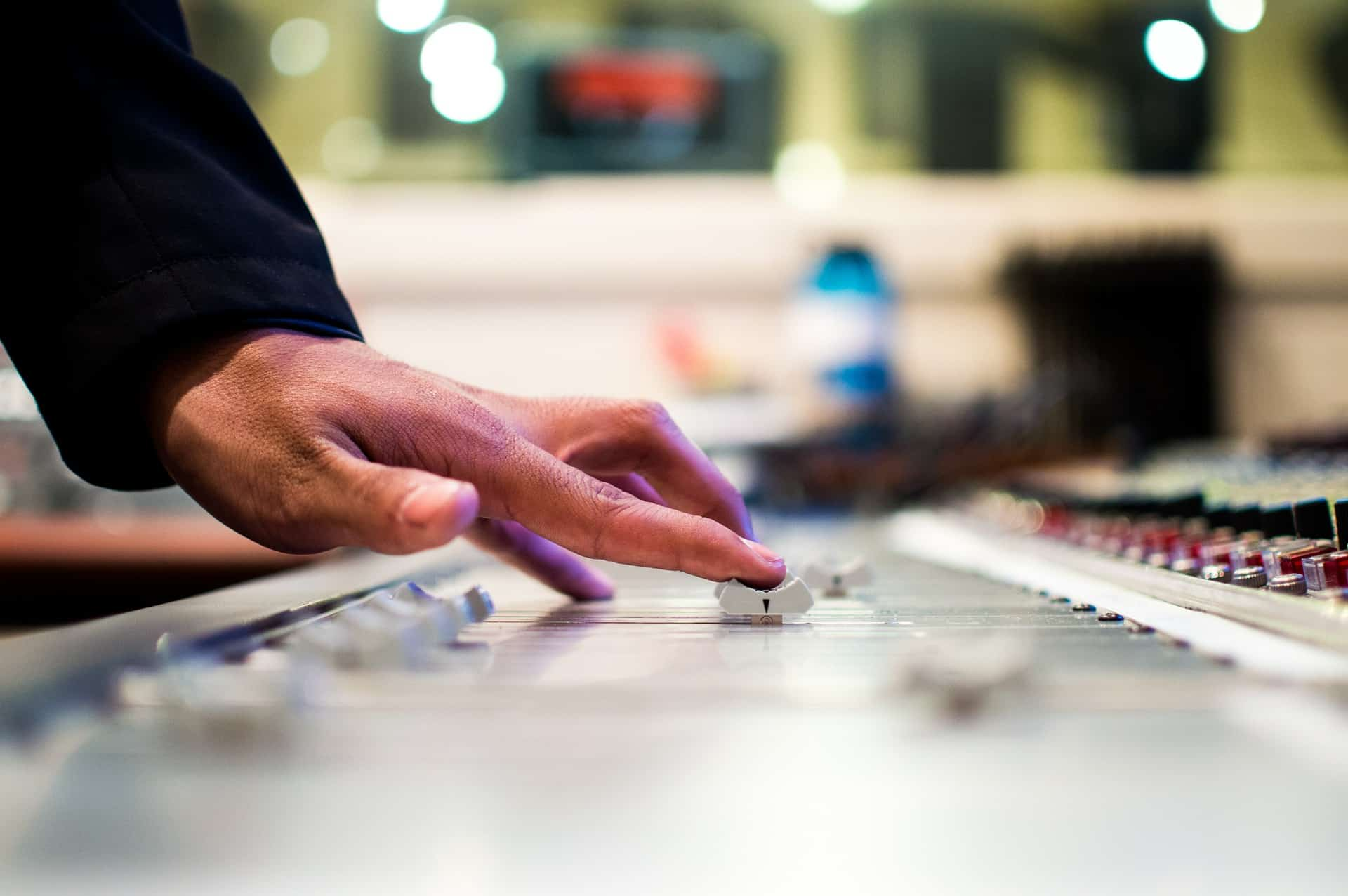 Close de uma mão controlando um botão da mesa de som.