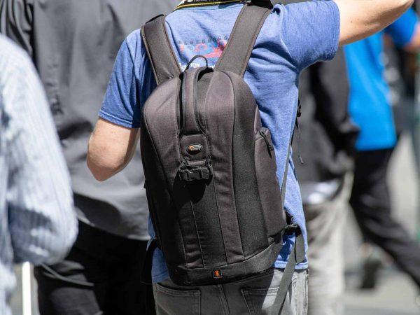 Imagem mostra uma pessoa vestindo uma camiseta azul com uma mochila nas costas.