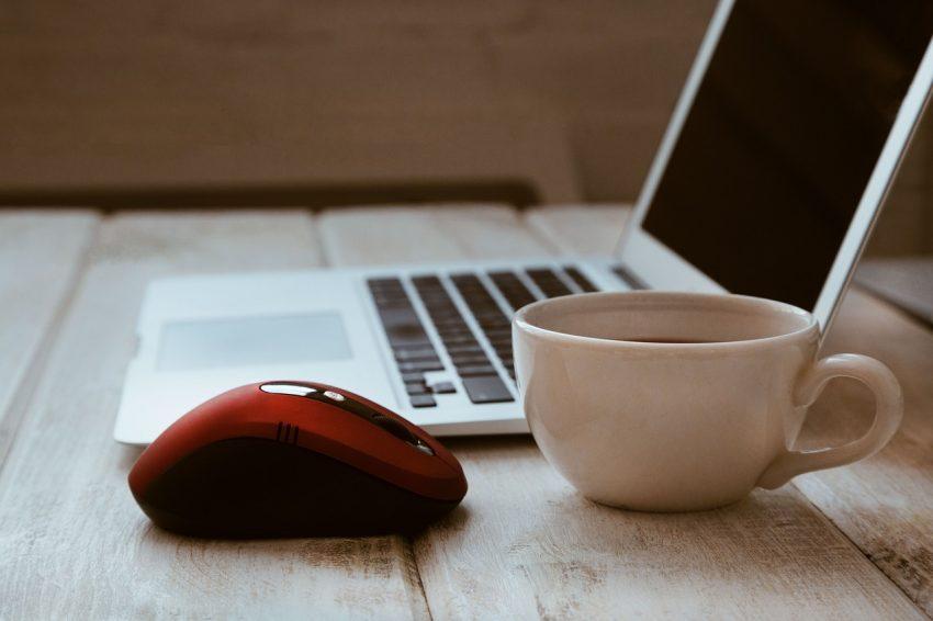 Imagem mostra mouse sem fio vermelho com notebook e café.