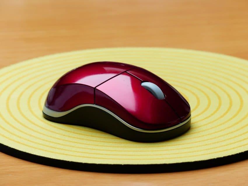 Imagem mostra mouse em close em cima de mouse pad amarelo.