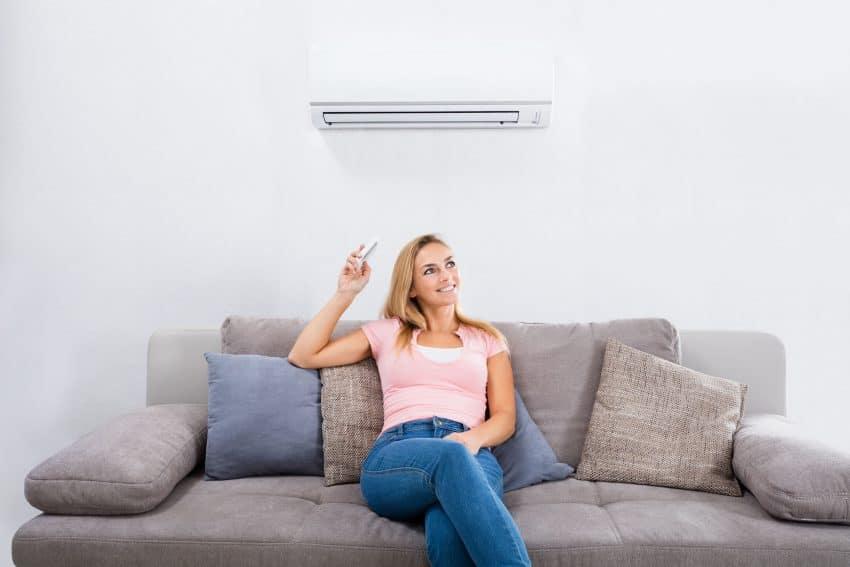 Imagem mostra mulher sentanda no sofá apontando controle para o ar condicionado.