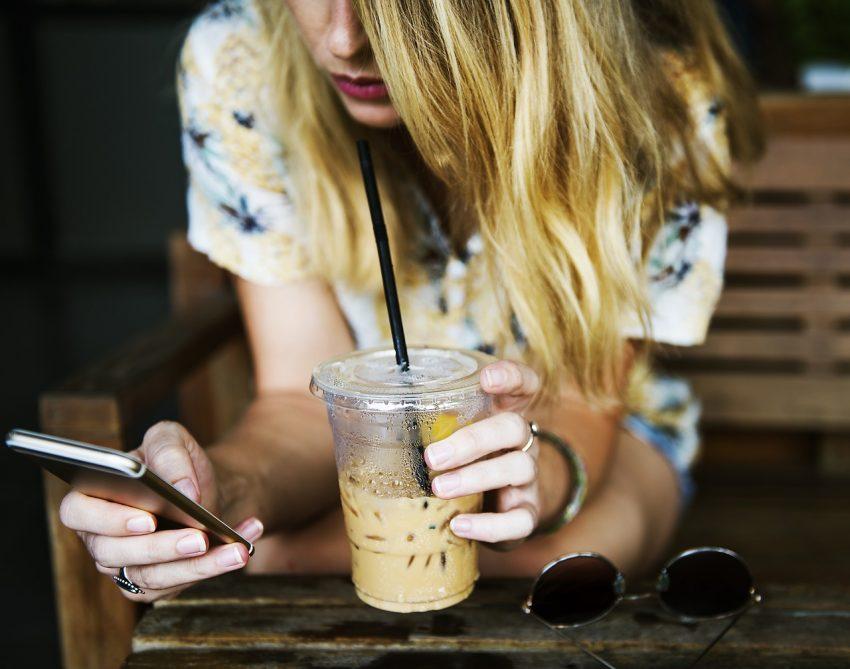 Imagem de uma moça segurando um café gelado e usando o smartphone.
