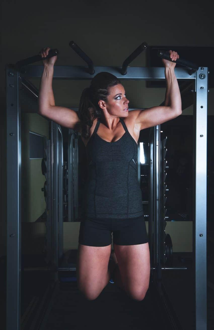 Garota faz exercícios com o auxílio de equipamento para musculação.