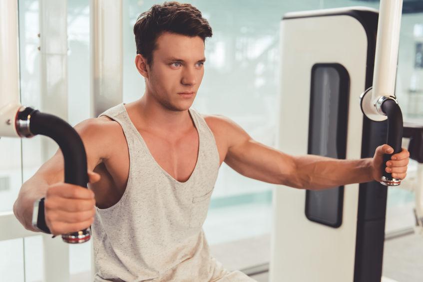 homem sentado utilizando máquina de musculação