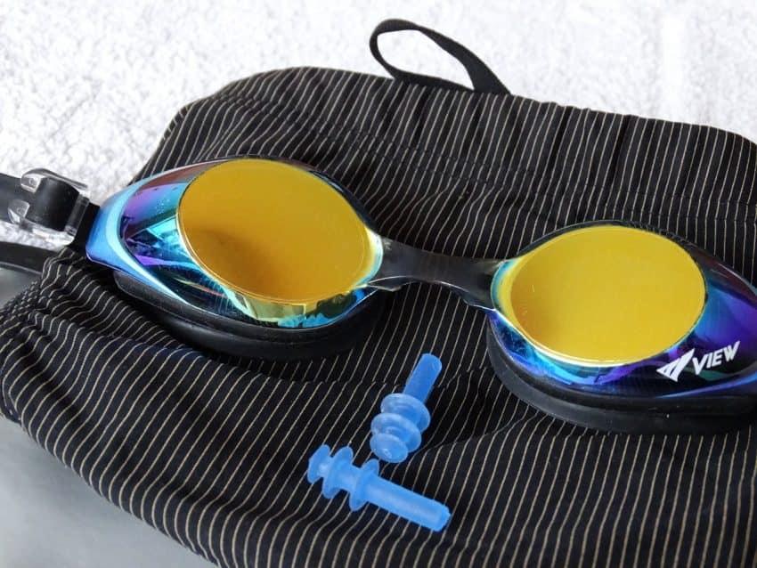Óculos, calção de banho e protetor de ouvido.