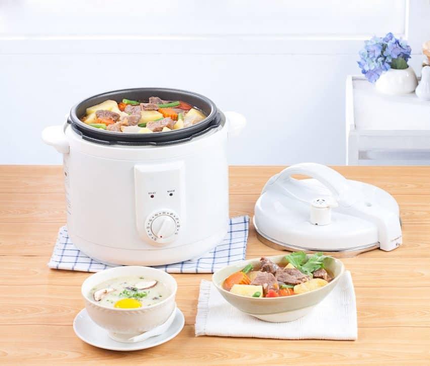 Imagem mostra panela de arroz elétrica com ensopado de carne e legumes.