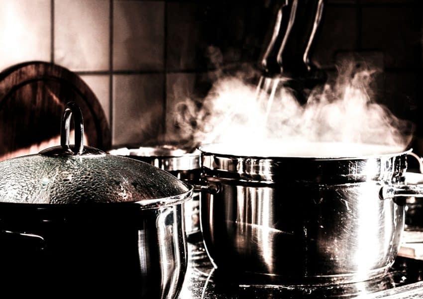 Panelas em cozimento no fogão com liberação de vapor.