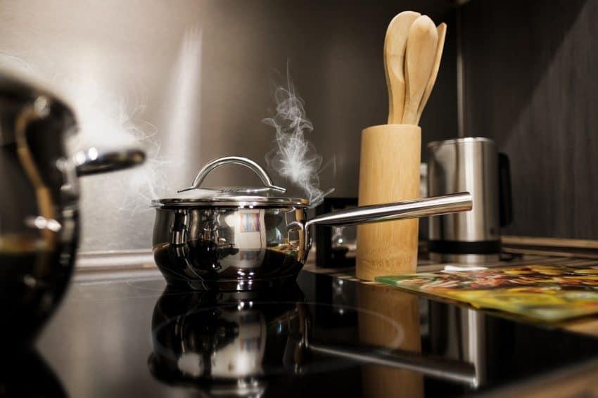 Imagem mostra panelas de aço inox no fogão.