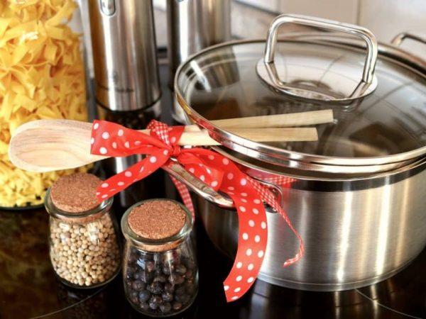Panela de aço inox com colher de pau decorativa e potes com especiarias.