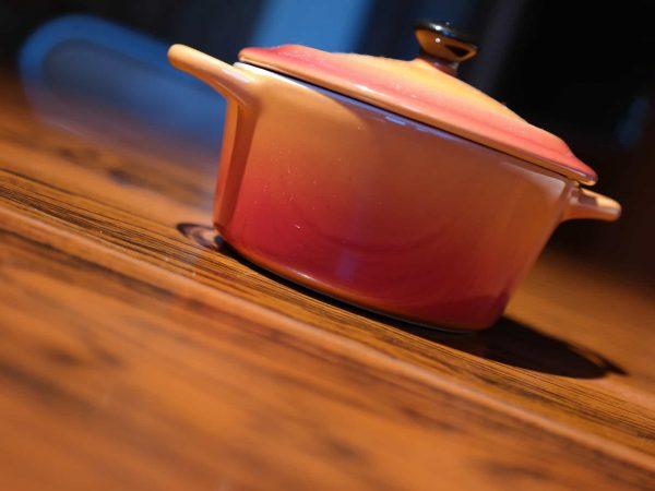 Imagem de uma panela avermelhada de cerâmica sobre uma mesa de madeira.
