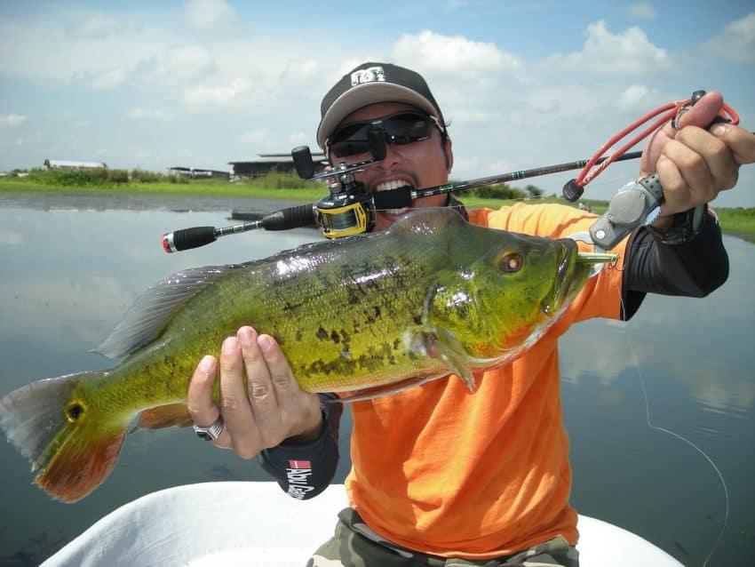 Pescador segurando peixe grande com alicate de pesca.
