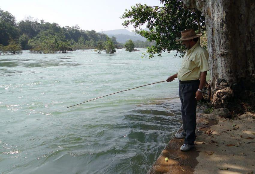 Pescador na margem de um rio utilizando uma vara de pesca em um local com bastante correnteza.