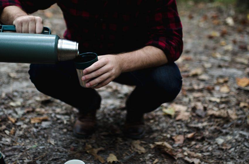 Imagem de uma pessoa enchendo um copo com uma bebida armazenada em uma garrafa térmica.