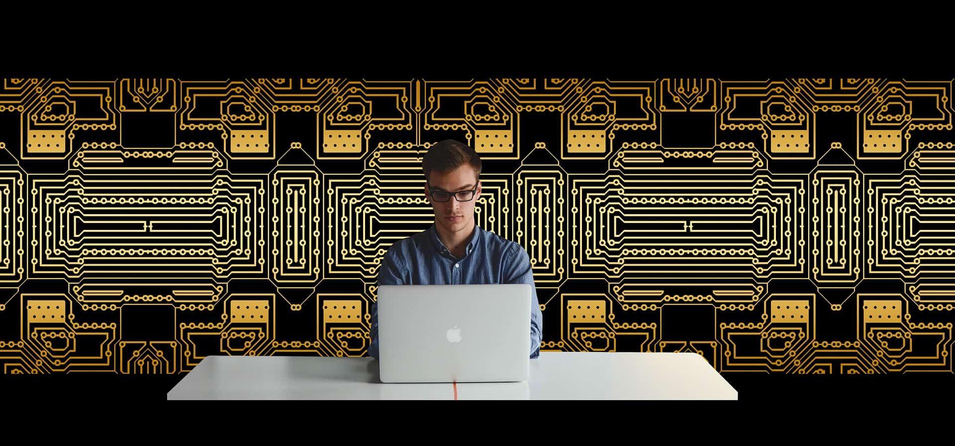 Imagem mostra homem com óculos à frente de um notebook, com fundo tecnológico.