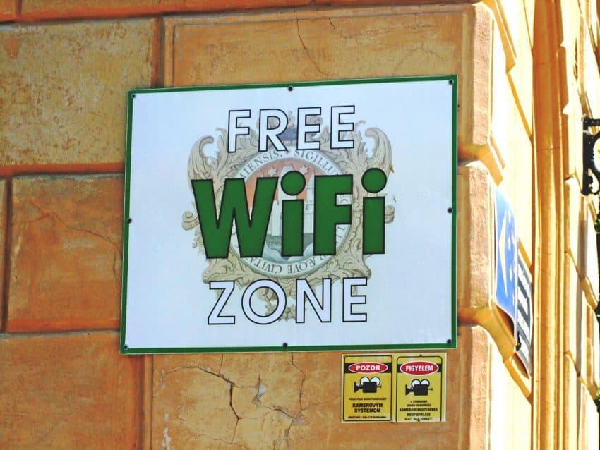 """Placa colada na parede dizendo """"Free Wifi Zone""""."""