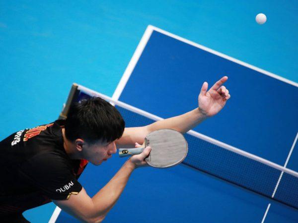 Imagem mostra jogador batendo em uma bolinha com sua raquete de tênis de mesa.