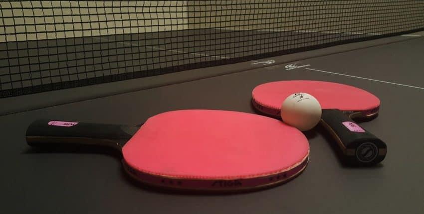 Imagem mostra duas raquetes e uma bolinha em cima de uma mesa de tênis de mesa.