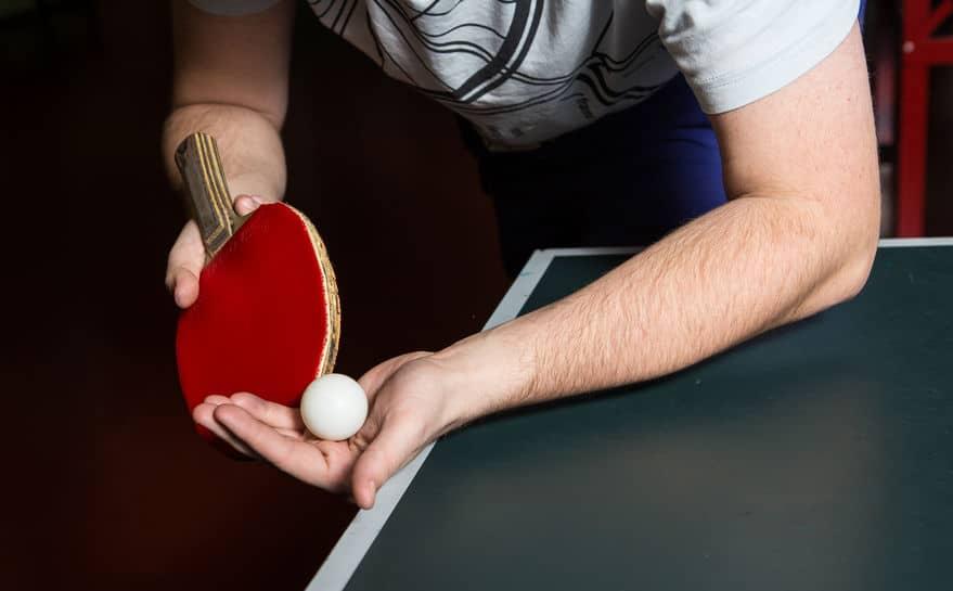 pessoa em close executando saque em tênis de mesa